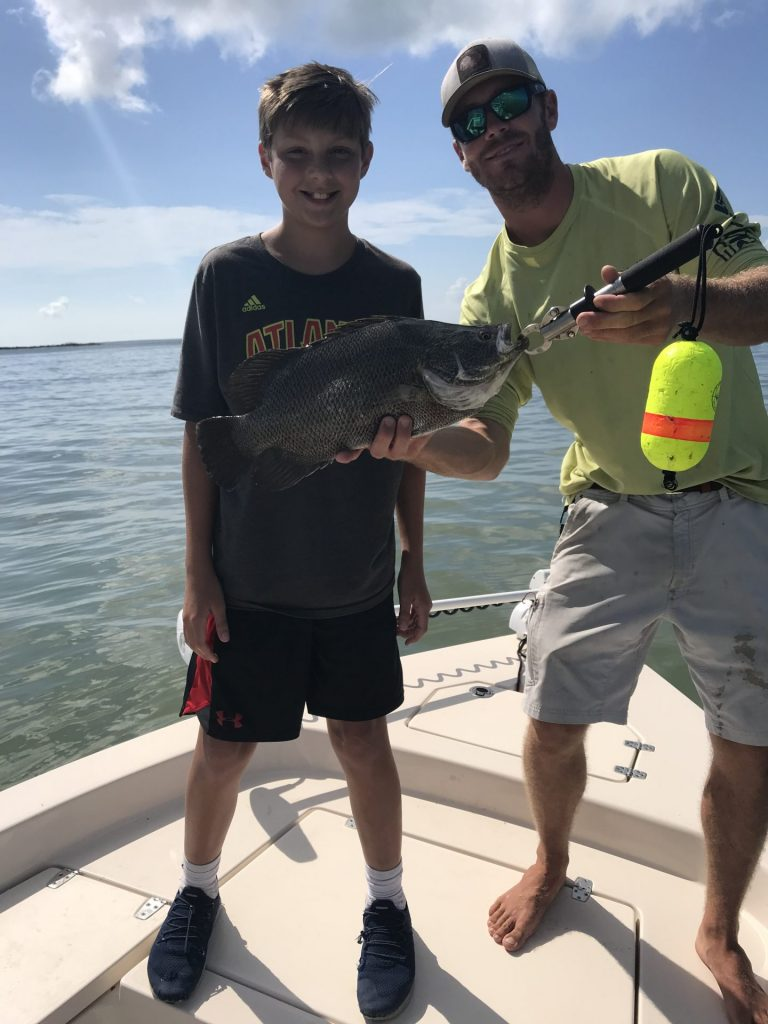 Captain Zach and young angler holding his catch