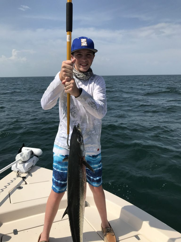 Young angler holding huge catch caught on charter trip